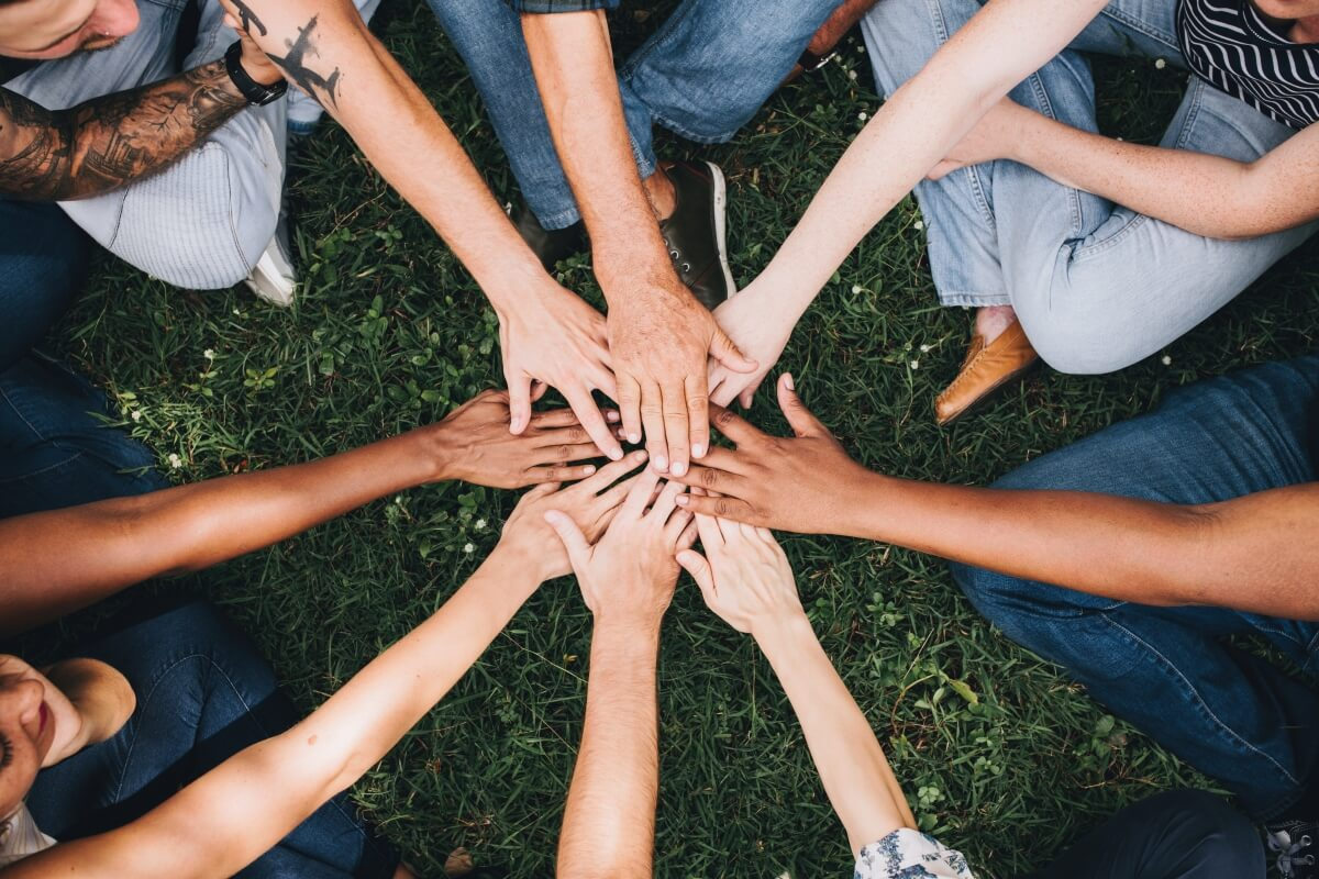 Group of people sitting in a circle and putting their hands in the middle